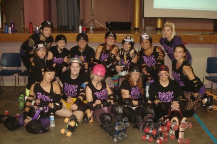 The Tragic City Rollers squad photo, with Voodoo Lily front and center in the pink helmet. (Neighbors of the Heart)